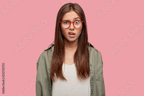 Valokuva  Indoor shot of indignant woman frowns face in displeasure, wears spectacles, shirt, models against pink background, doesnt like something dressed in casual shirt