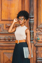 Young African American College Student With Afro Hairstyle, Eye Glasses, Wearing Sleeveless Light Color Top, Black Skirt, Belt, Holding Laptop Computer, Standing By Vintage Office Door In New York..