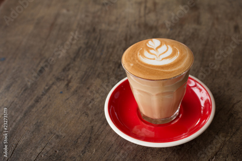 Piccolo Latte art in small glass with red ceramic plate topping beautiful flower Fototapet