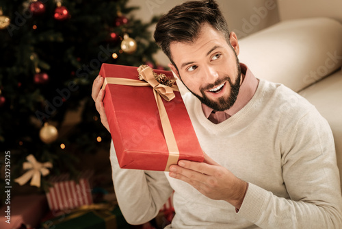 What is inside. Cheerful happy positive man holding a present and trying to guess what is inside while feeling excited about it