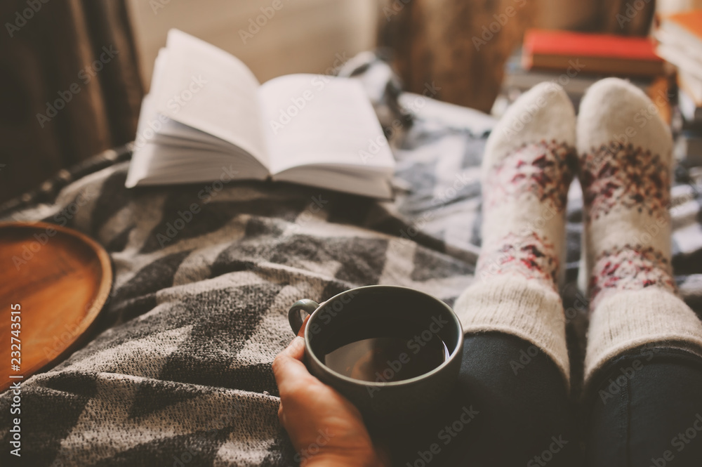 Fototapety, obrazy: cozy winter day at home with cup of hot tea, book and warm socks. Spending weekend in bed, seasonal holidays and hygge concept
