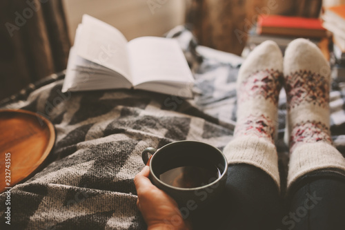 cozy winter day at home with cup of hot tea, book and warm socks. Spending weekend in bed, seasonal holidays and hygge concept