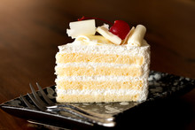 Piece Of White Cake With Vanilla Frosting And Cherry Jelly, Topped With White Cheese