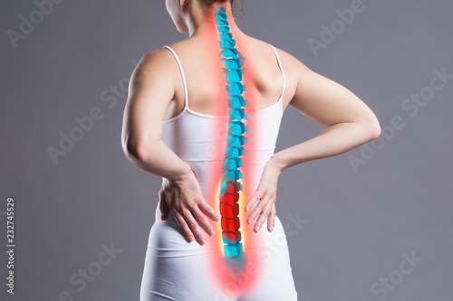 Fototapeta Pain in the spine, woman with backache on gray background, back injury