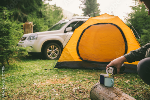 Poster Camping man hand pour tea in metal cup. yellow tent with suv on background