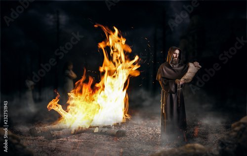 Photo  Medieval monk reads a prayer against a big fire