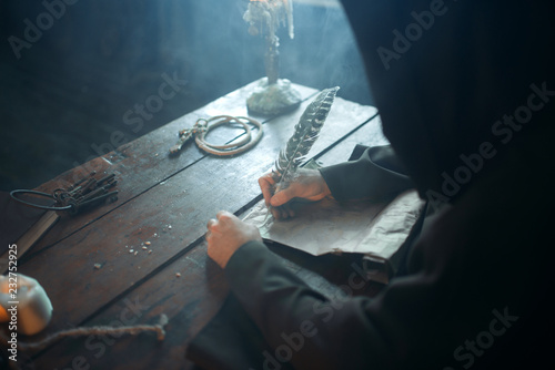 Fotografía Medieval monk sitting at table and write, top view