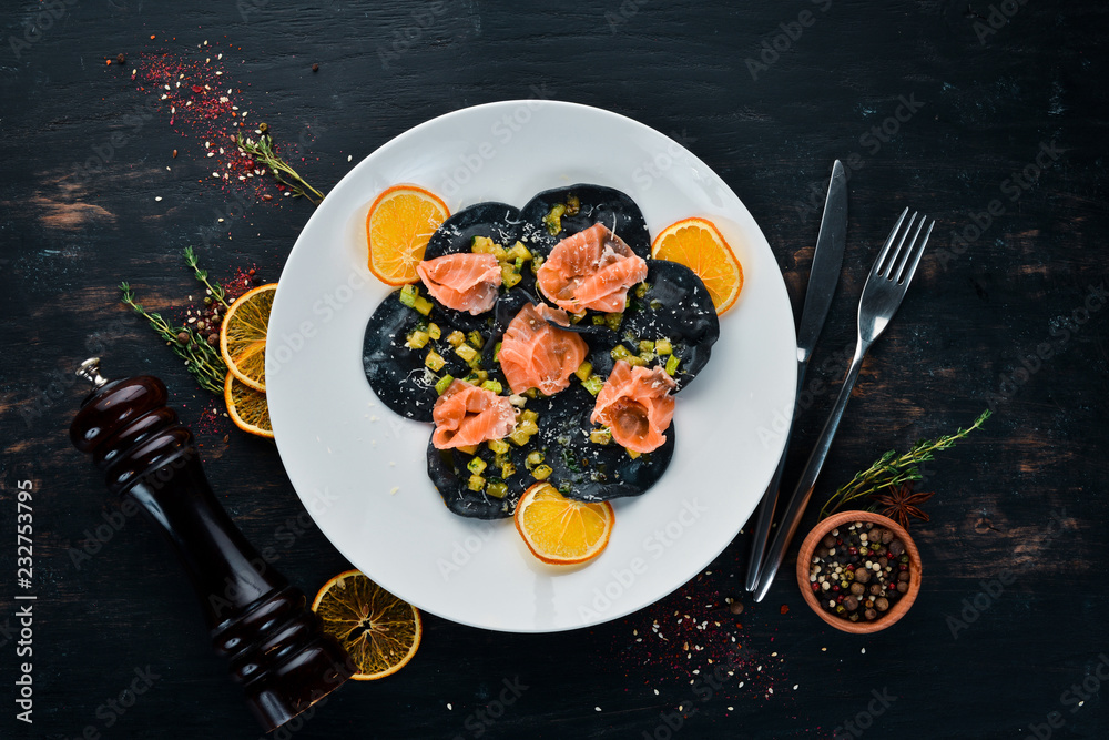 Fototapety, obrazy: Black ravioli with salmon and parmesan cheese. In a plate on a wooden background. Top view. Free copy space.