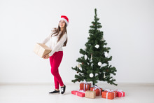 Christmas And Holidays Concept - Young Woman In Santa Hat Holding Stack Of Gift Boxes Over White Background