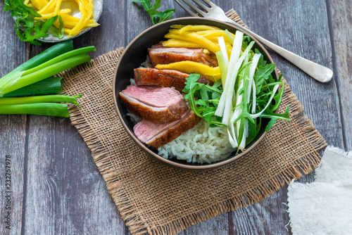 Hoisin duck with mango, spring onion, rocket lettuce salad and rice - top view