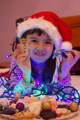 little girl with christmas lights and gingerbread cookies