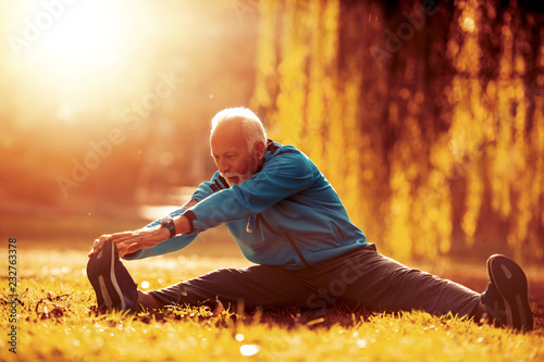 Staande foto Wanddecoratie met eigen foto Senior man stretching in the park