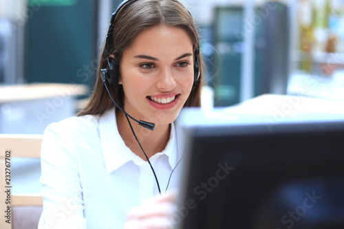 Fotografía Female customer support operator with headset and smiling.