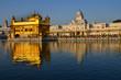 インドのパンジャブ州 アムリトサルの黄金寺院 朝日を浴びて輝く建物 巡礼するシーク教徒の列