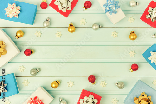 Fototapety, obrazy: Copy space on a light blue plank background. Around a lot of small gift boxes and Christmas balls.