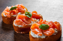 Canapes With Smoked Salmon And Cream Cheese On Wooden Table Background