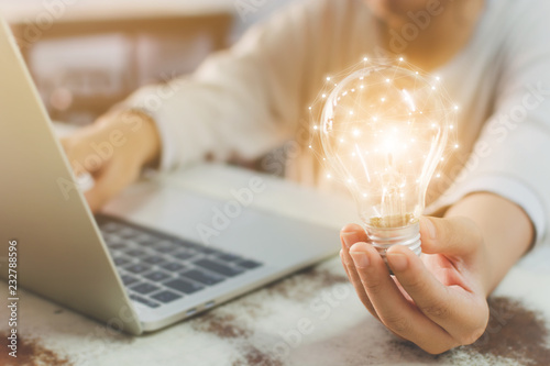 Fotografía Woman hand holding light bulb and using laptop on wooden desk