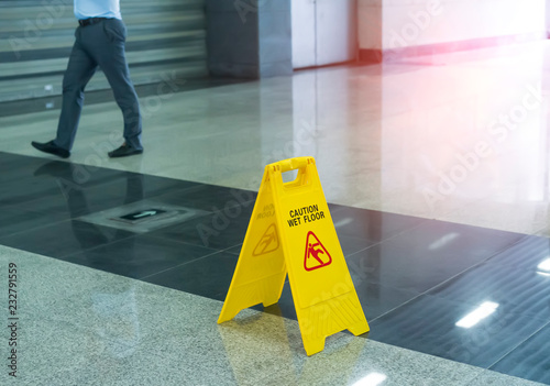 Fotografiet Yellow Caution wet floor sign on wet floor