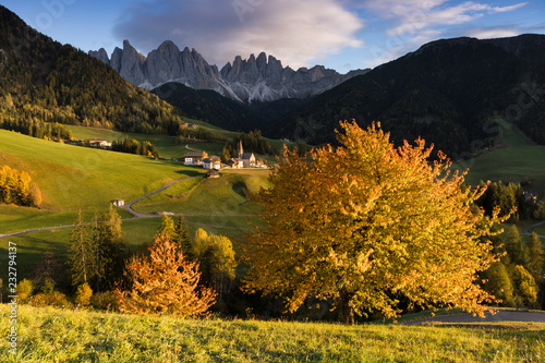 the typical autumnal landscape in Villnössertal with the famous alpine village and Geisler Group in the background, Bolzano province, South Tyrol, Trentino Alto Adige, Italy