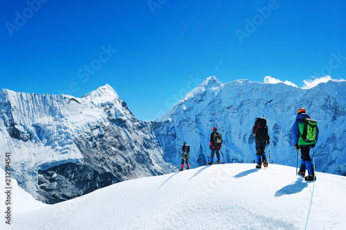 Canvas Print Hikers with backpacks reaches the summit of mountain peak