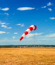 Red And White Windsock Wind Sock On Blue Sky On The Aerodrome, Yellow Field And Clouds Background In Autumn