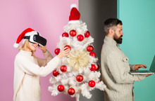 Technology, Virtual Reality, Family, Winter, Christmas Concept. Happy Couple Celebrate Christmas Holiday. Woman In Virtual Reality Glasses, Man With Laptop At Christmas. Family In Near Christmas Tree.