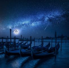 Fototapeta Swinging gondolas in Venice at night with stars, Italy