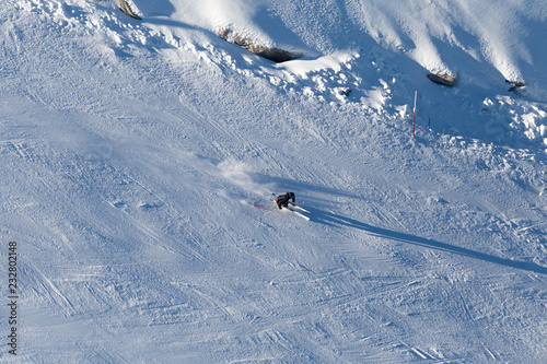 Downhill skiing, aerial view. Woman skier in mountains