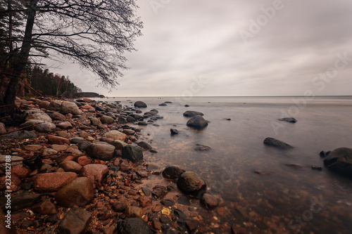Spoed Foto op Canvas Diepbruine long exposure sea beach with rocks and washed out waves of water