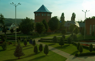 The high hexagonal tower of red brick and other buildings in the city park in the summer.