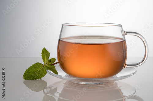 Staande foto Thee Black or green tea. clear tea glass with mint leaf on the saucer with transmitted light and reflection