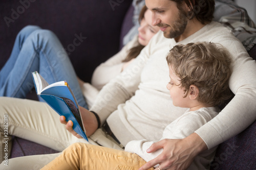 Young family sits on couch in living room at home Wallpaper Mural