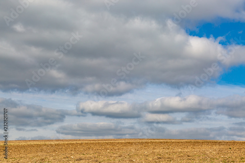 A ploughed field in Sussex with storm clouds overhead