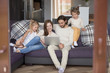 Married couple and little children sitting on couch in living room. Parents with little daughter, son looking at computer and smiling. Happy young family together at home watching funny videos online