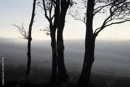 Beautiful foggy sunrise landscape over the tors in Dartmoor revealing peaks through the mist