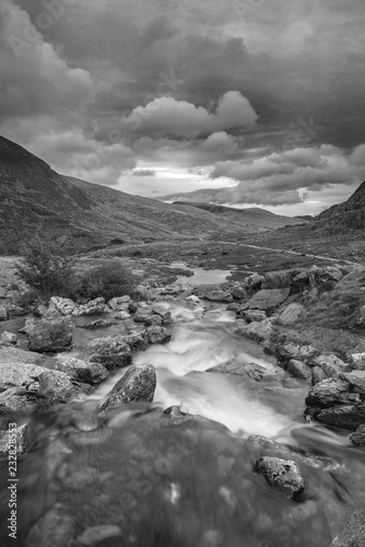 Moody landscape image of river flowing down mountain range near Llyn Ogwen and Llyn Idwal in Snowdonia in Autumn
