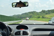 Driving on a highway that goes through beautiful countryside in summertime with other vehicles in his direction beside him