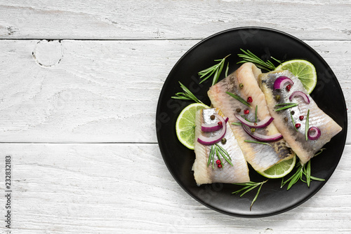 herring fillet with pepper, rosemary, onion and lime on black plate on white background. top view with copy space