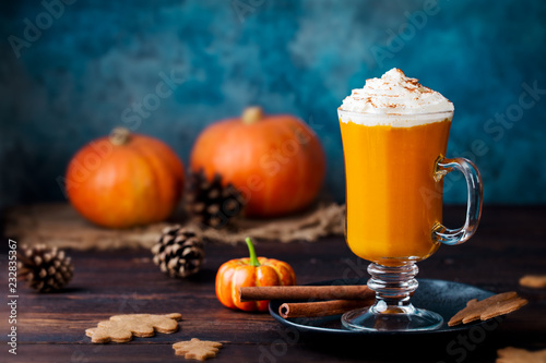Pumpkin spice latte, smoothie with whipped cream. Wooden background. Copy space.
