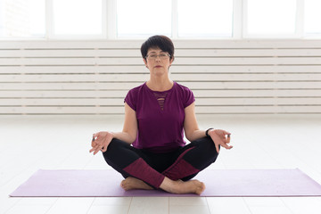 Fototapeta Yoga, harmony, people concept - Middle aged woman sitting in lotus position