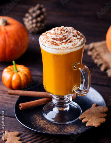 Pumpkin smoothie, spice latte. Boozy cocktail with whipped cream. Wooden background.