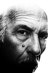Highly detailed, high contrast, close up, black and white portrait of man with head turned looking at viewer. Visible grain at 100%