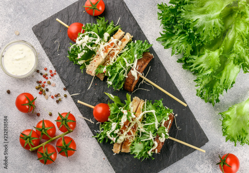 Fotografía  Delicious skewers of lettuce, chicken, cherry tomato, cheese and Caesar sauce