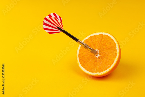 Fotografie, Obraz  orange slice, fruit with circular target marked and dart on yellow background