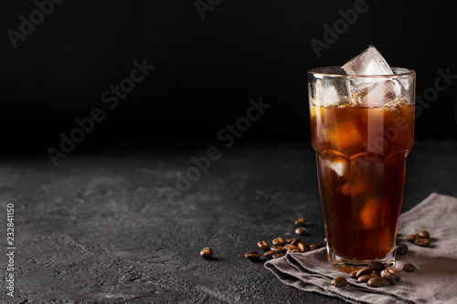 Stampa su Tela tall glass cold brew coffee with ice on black or dark background