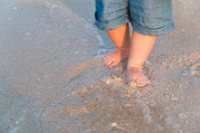 Bare Feet Walking At Sandy Beach Near The Sea. Little Baby In Blue Jeans Shorts Going To Touch The Sea At Sunset. Wave Washes Baby's Feet. Toned. Soft Focus.