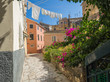 Corfu old town narrow cobble stone street with pink Bougainvillea flowers, traditional greek houses with hanging drying white laundry, blue sky summer sunny day