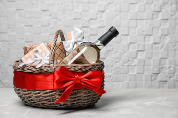 Gift basket with bottle of wine on light background. Space for text