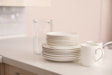 Fototapeta Stack of clean dishes, cups and glass jug on table in kitchen