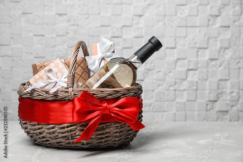 Gift basket with bottle of wine on light background Fototapeta